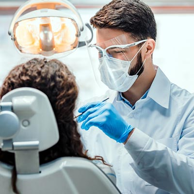 Dentist wearing a face shield and face mask performs a dental procedure on a patient